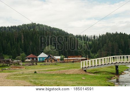 Landscape of houses located near mountains and forests. Bridge over river. Mountain Altai. Russia.