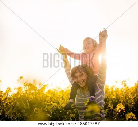 Cheerful young mother carrying kid on shoulders