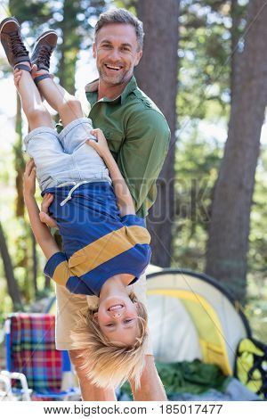 Portrait of cheerful father holding son upside down at campsite