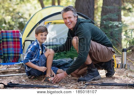 Portrait of cheerful father and son kneeling by tent in forest