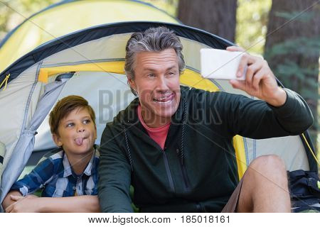 Playful father and son making faces while taking selfie in tent