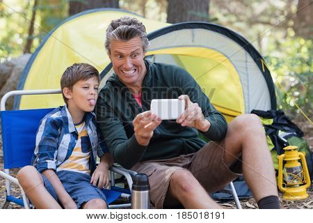 Happy father and son taking picture by tent in forest