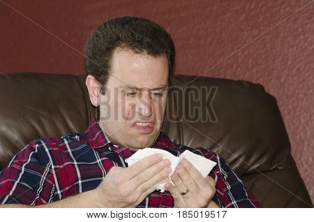 Disgusted man with a cold looking at his tissue after blowing his nose.