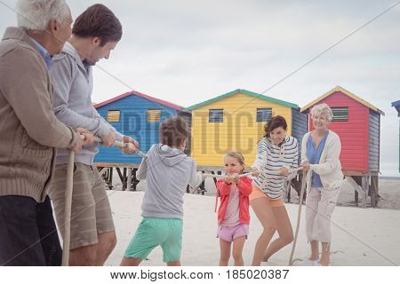 Family playing tug of war at beach against sky