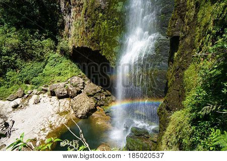 A double rainbow in front of a cliffside waterfall running alongside a cave