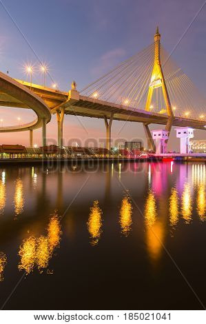 Suspension bridge over watergate with water reflection light in the river Bangkok Thailand