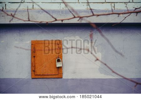 Brown hatch with the lock on the blue-violet wall. There trees branches. Grunge wall. Vintage.