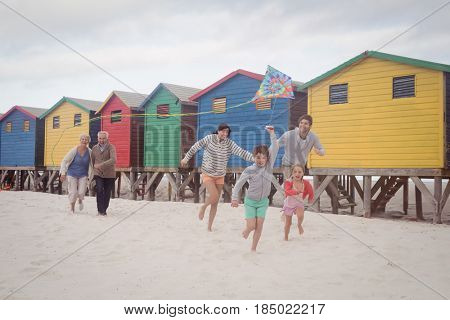 Happy multi-generation family running by beach huts on sand at beach