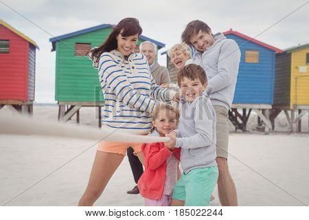 Multi-generation family playing tug-of-war at beach