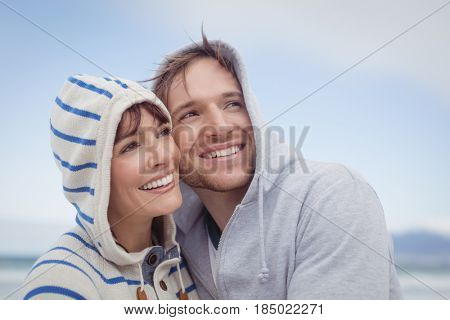 Smiling couple wearing hooded sweater while looking away at beach during winter