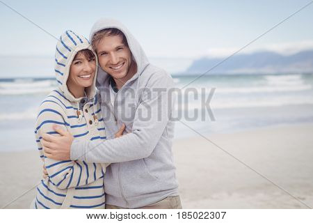 Portrait of smiling couple wearing hooded sweater at beach during winter