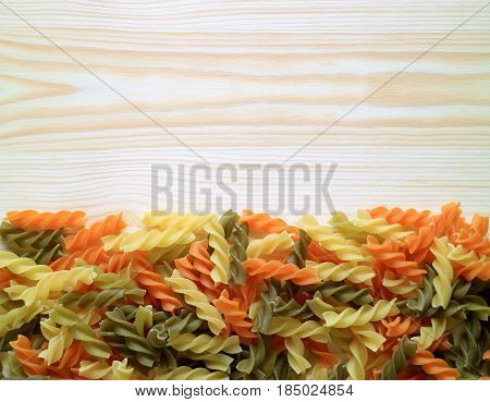 Uncooked Three-color Fusilli Pasta on the Wooden Table, Horizontal Top View Photo with Free Space for Text or Design