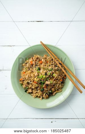 Fried rice with chopsticks. Basil chicken fried rice with chopsticks on a white wooden background viewed from above. This thai inspired meal is perfect for a quick lunch or served as side dish.