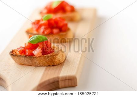 Tomato bruschetta crostini. Bruschetta is an italian food made of chopped tomatoes garlic basil and fresh herbs on a toasted bread. These are traditionally served as snacks or antipasti (appetizers).