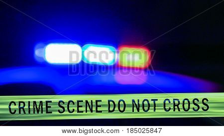 Close-up on siren on police car flashing with crime scene boundary tape Defocused poster