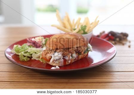 Save Download Preview French fries and big burger. Junk food on brown table. Well made burger in cafe. Example of popular junk food.