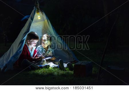 Cute Little Brothers, Playing On Tablet And Telephone At Night In Campside