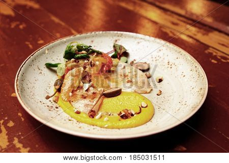 Seafood starter with orange slices and pumpkin mash on old wooden table, toned image