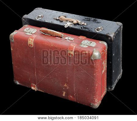 Closeup of two battered old suitcases against black background