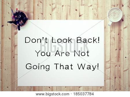 Inspiring motivation quote handwritten on a notepad don't look back you are not going that way. White pad paper image.