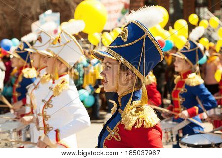 Khabarovsk Russia - May 1 2017: Young pretty girls playing drums and marching at music festival. Female drummers orchestra wearing hussar costumes at a parade