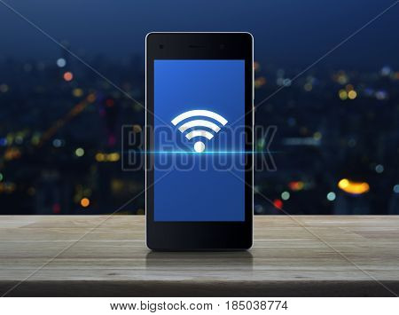 Wi-fi connection icon on modern smart phone screen on wooden table over blur colorful night light of city tower Technology and internet concept