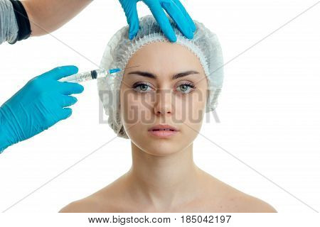 a young girl with a hat on his head and she looks directly make facial filler injections isolated on a white background close-up