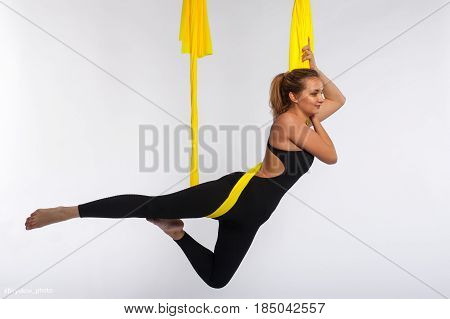 Young yogi woman doing yoga practice in yellow hammock in studio. Female blonde girl performing aero yoga or aerial acrobatics. Body balance and antigravity training. Wellness and body care concept.