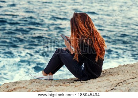 Young redhed woman with curly hair relaxing and messaging on rocky coast at sea loneliness wireless technology