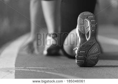 Athlete runner feet running in the Park on the track closeup on shoe, white and black