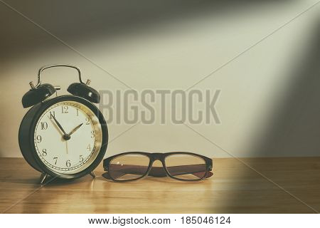 Alarm clock and glasses on wooden table. Vintage style.