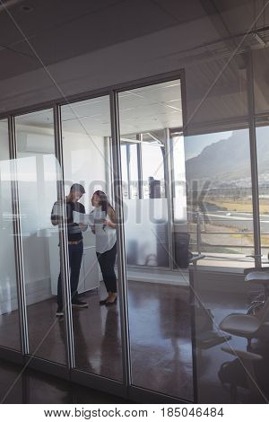 Full length of business colleagues dicussing over documets at office seen through glass