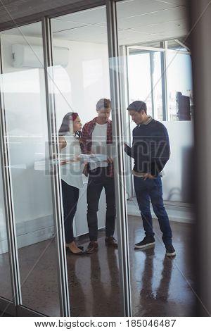 Full length of business colleagues seen through glass dicussing at office