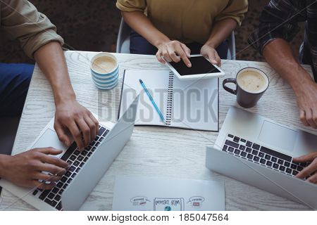 Mid section of creative team using laptop and digital tablet while planning in office