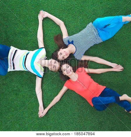 Young smilling women lying on green grass .