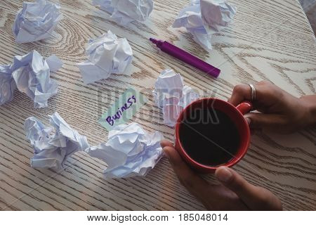 Cropped hand of businesswoman holding coffee by crumpled papers on desk in office