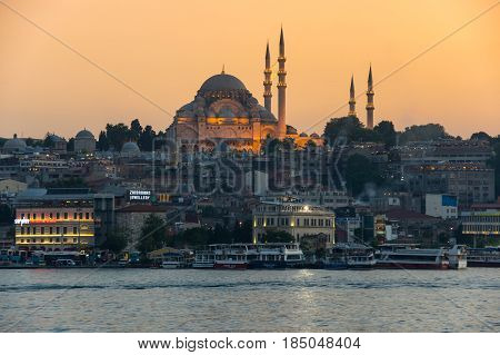 ISTANBUL TURKEY - JUNE 20 2015: Night view on the Suleymaniye Mosque and fishing boats in Eminonu Istanbul Turkey