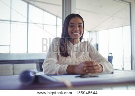 Portrait of young businesswoman sitting at workbench in office
