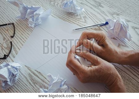 Close up of businesswoman crumpling papers on desk in office