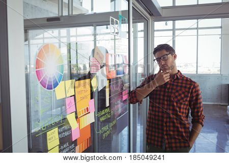 Thoughtful young businessman looking at adhesive notes in creative office