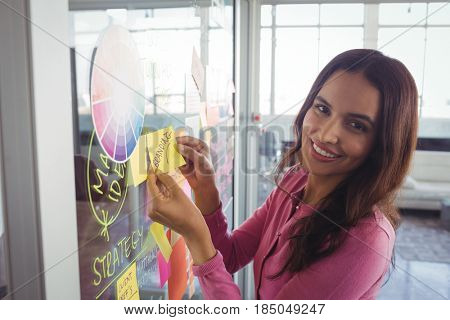 Portrait of smiling female designer holding adhesive note on glass in creative office
