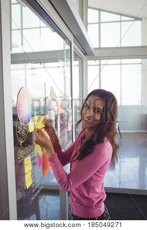 Portrait of smiling female designer planning with adhesive notes on glass in creative office