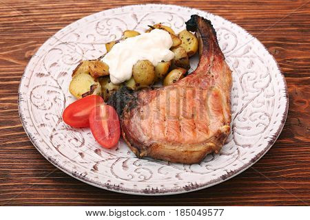 Pork Chop with potatoes and vegetable on wooden background