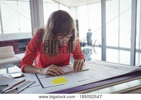 Focused female interior designer working in brightly lit office