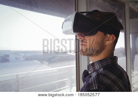 Close up of young businessman wearing vr headset by window in office