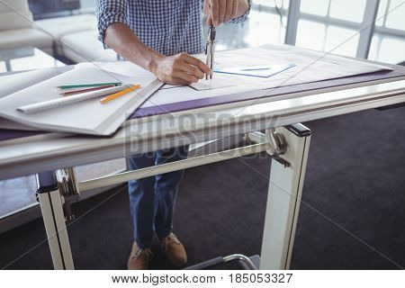Low section of male interior designer making diagram on papers in office