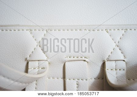 Top view of white leather and details of seams close-up. Things made of leather, texture and details of the product. Macro shooting texture and seams leather bag. Soft focus, beautiful bokeh.