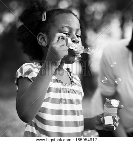 African descent girl is playing bubble maker