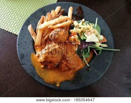 Meatballs with spicy tomato sauce on a plate side with french fries and spinach feta white cheese and tomato salad on black plate Roasted meatballs in sweet and sour tomato sauce close up top view