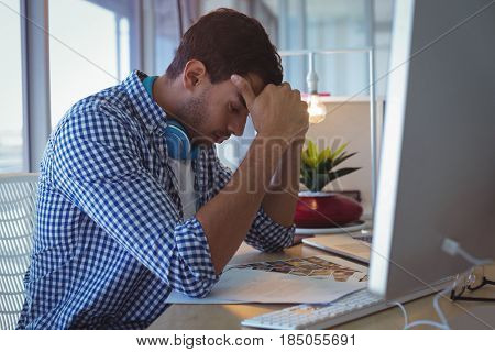 Tensed designer with head in hand sitting in ofice